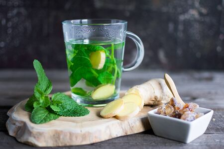 Fresh mint and ginger tea served with sugar candy on a decorative wooden board. Standard-Bild - 136761692