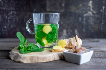 fresh tea with mint leaves, ginger bulb and rock sugar on decorative wooden board Standard-Bild - 136761660