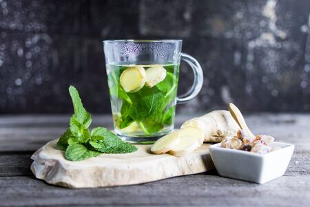Tea with fresh mint and ginger pieces on a wooden board. Ideal as an eye-catcher. Standard-Bild - 136761620