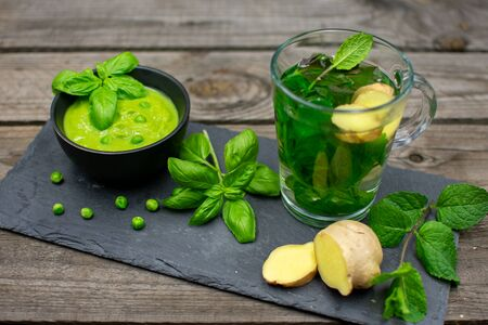 Mint-ginger tea and pea cream soup served with basil on a slate plate. Standard-Bild - 136762225
