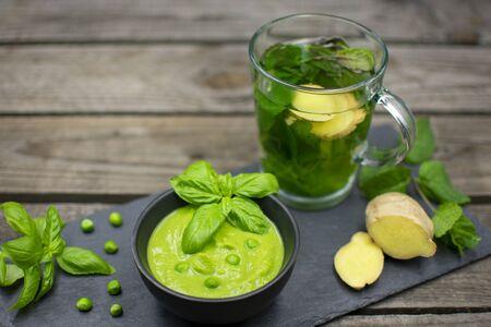 Pea cream with basil on black slate. With a mint - ginger tea. Standard-Bild - 136762529