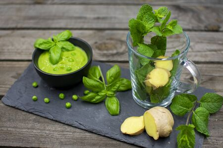 empty teacup with fresh mint and ginger slices. In addition, a delicious pea cream with basil