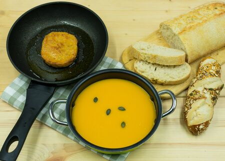 Pumpkin soup in a pot, patty in a pan with ciabatta and pumpkin seed rolls