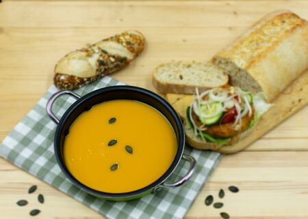 Pumpkin soup in a pot next to a patty on bread with tomatoes, onions and lettuce. Standard-Bild