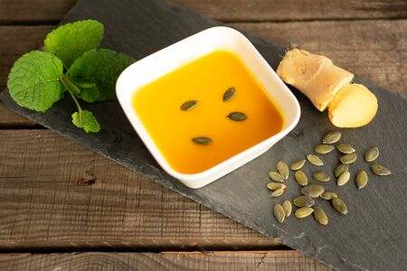 delicious pumpkin soup in a soup bowl with ginger, pumpkin seeds and mint Standard-Bild