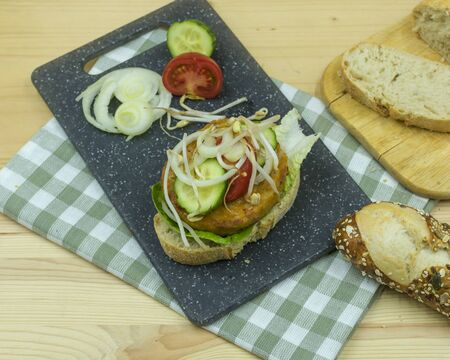 healthy tofu patties on ciabatta bread with tomatoes, onion cucumber and lettuce. In close-up Standard-Bild - 136763198