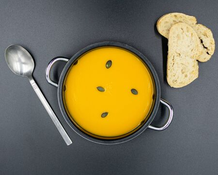 frische Kürbissuppe im Teller mit schwarzem Hintergrund. Ansicht von oben.