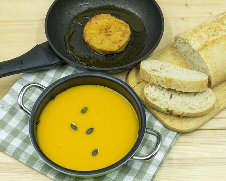 Pumpkin soup in a pan, patties in a pan and bread Standard-Bild - 136763214