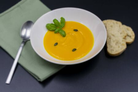 fresh pumpkin soup in pot on green napkin with black background. View from above. Standard-Bild
