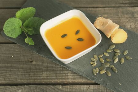 delicious pumpkin soup in a small bowl with ginger, pumpkin seeds and mint Standard-Bild
