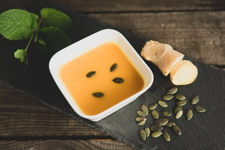 Pumpkin soup with ginger, pumpkin seeds and mint on a slate plate Standard-Bild