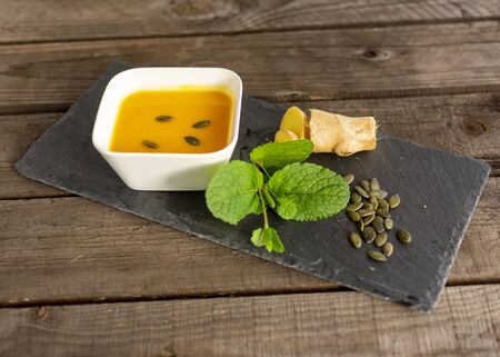 delicious pumpkin cream soup with ginger, pumpkin seeds and mint decorative on a slate plate