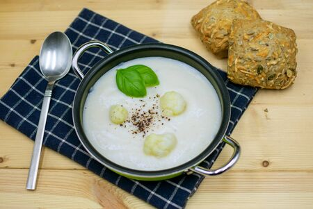 Cauliflower soup in a pot with bread rolls and napkin on wood Standard-Bild