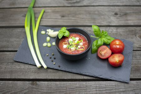 Mediterranean tomato soup in a small bowl, decorated with garlic, spring onions and basil.