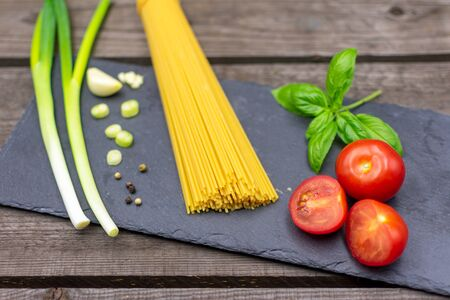 raw spaghetti decorated with spring onions, basil, tomatoes and garlic. Mediterranean food