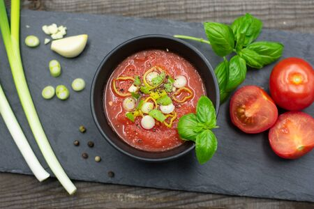 Mediterranean tomato soup in a small bowl with spring onions, pepper and basil. View from above