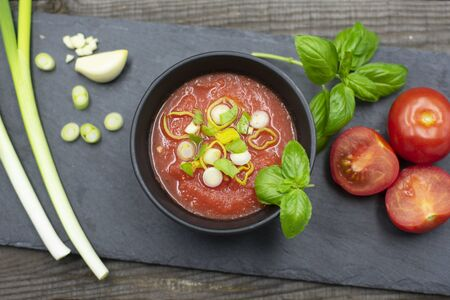 Mediterranean tomato soup in a bowl decorated with spring onions and basil. View from above
