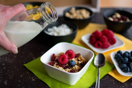 Bowl of healthy muesli into which one hand would like to pour from a bottle of milk