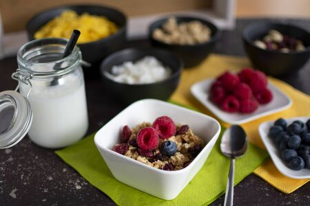 Bowl of delicious muesli. Served with coconut milk in a jar and ingredients for the muesli