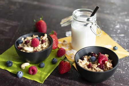 Two bowls of muesli with fresh berries. In addition, coconut milk in a mason jar with a straw