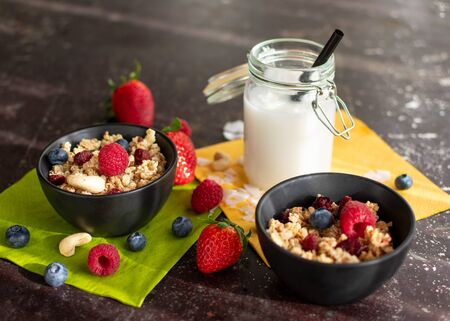 Muesli with fresh berries in black bowls. In addition, coconut milk in a mason jar with a straw