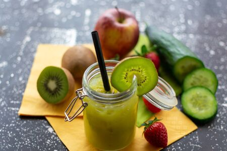 green smoothie in a jar with crushred ice and kiwi slice. With ingredients in the background
