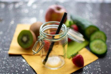 empty preserving jar in close-up. Fresh fruit and vegetables in the blurred background.