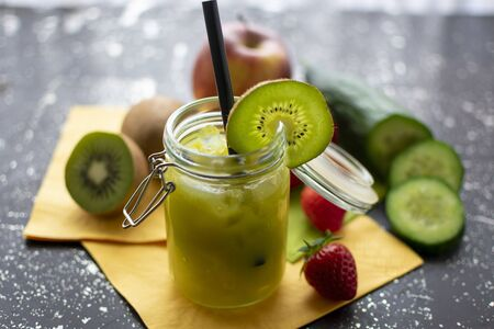green smoothie in a jar with crushred ice and kiwi slice. With the ingredients in the background Standard-Bild