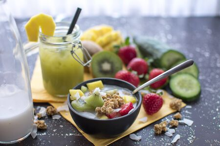 healthy breakfast: crispy muesli with fresh strawberries, kiwi, mango and coconut flakes with coconut milk Served with a smoothie in a preserving jar