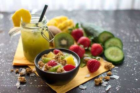 healthy breakfast: crispy muesli with fresh strawberries, kiwi, mango and coconut flakes with yoghurt Served with a smoothie in a preserving jar  Standard-Bild