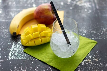 empty glass with crushed ice and straw. Fresh fruit in the background Standard-Bild