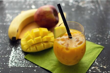 delicious smoothie with mango in a glass with crushed ice and straw Fresh fruit in the background Standard-Bild