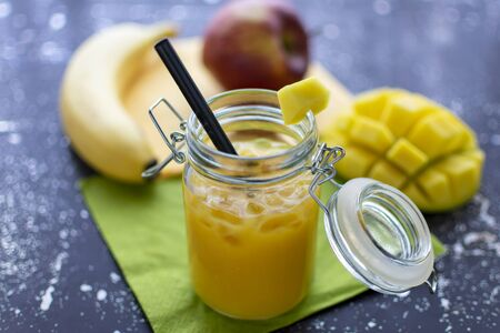 delicious smoothie with mango in a jar with straw and crushed ice. Fresh fruit in the background