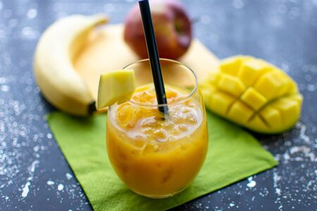 tasty mango smoothie with crushed ice and straw in a drinking glass Fresh fruit in the background