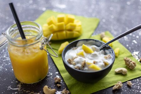 Yoghurt with crunchies, cashew nuts and fresh mango pieces. served with a mango smoothie with crushed ice  Standard-Bild