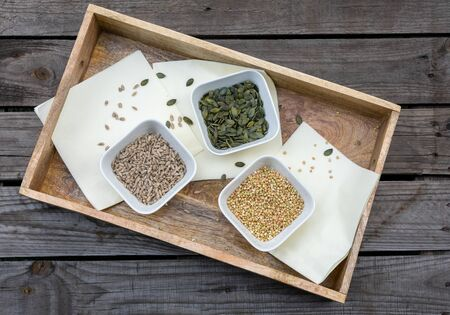 rustic wooden tray with bowls filled with pumpkin seeds, buckwheat and sunflower seeds on light-coloured napkins On wooden pallet Reklamní fotografie - 141685106