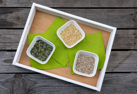 Tray with bowls filled with pumpkin seeds, buckwheat and sunflower seeds on rustic wooden pallet Reklamní fotografie - 141685346