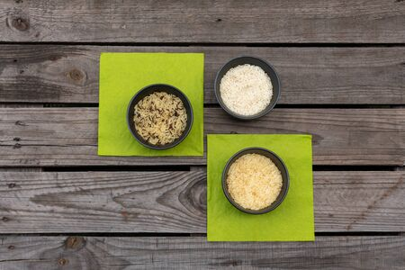 Wild, basmati and long grain rice in bowls on rustic wooden pallet with green napkins Reklamní fotografie - 141685366