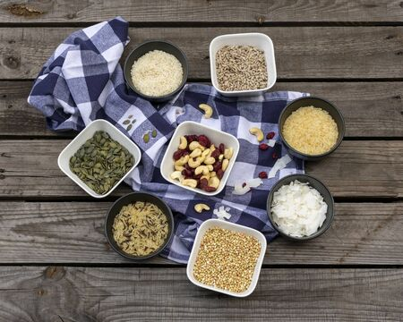 different kinds of grains and rice in small bowl with blue and white chequered napkin on a wooden pallet