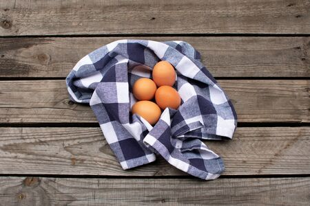 brown eggs in a blue and white checked napkin on a wooden pallet Standard-Bild