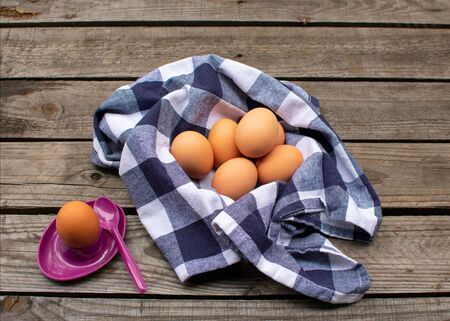 brown eggs in a blue and white checked napkin, next to it an egg in a purple egg cup. On a wooden pallet Reklamní fotografie - 141685686