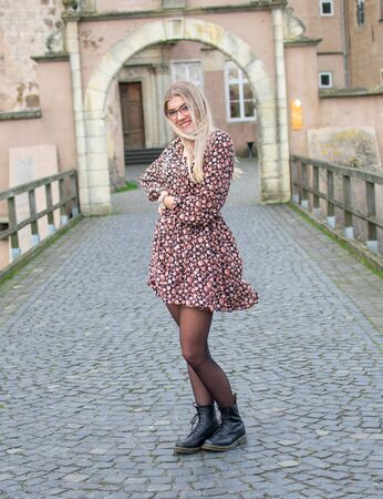 Laughing, young woman wearing glasses with flowing, long, blond hair in a flower dress with laced ankle boots on an old stone bridge Standard-Bild