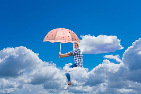 young woman sitting smiling on a cloud with an umbrella in her hand Standard-Bild - 146453396
