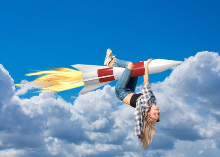 Young woman hangs on a rocket and flies with it through the clouds Reklamní fotografie - 145492111