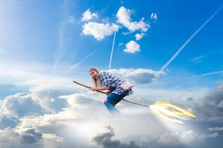 young, modernly dressed woman flies through the clouds on a witches broom with a trail of fire