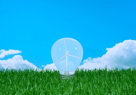 A wind power plant in a light bulb for clean energy. The bulb stands on a green meadow with a cloudy sky. 3d rendering