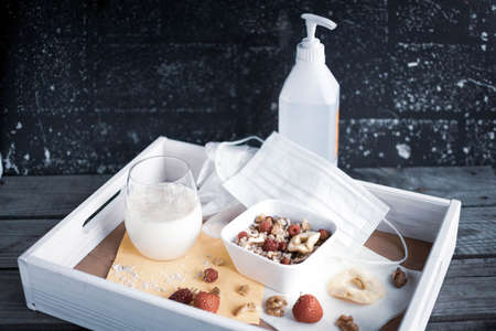 Wooden tray with healthy muesli, oat milk and hygiene products for Covid-19