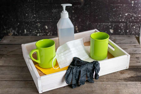 Wooden tray with two cups between which hygiene items such as a mouthguard, disposable gloves and disinfectant are placed. Reklamní fotografie - 150669223