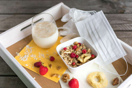 Wooden tray with healthy muesli, oat milk as well as a face mask and disposable gloves Standard-Bild
