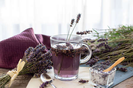 Lavender tea rustic on wood in a glass teacup. Lavender (Lavandula angustifolia), has a calming and antispasmodic effect.